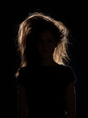 woman with tousled hair in black shadow