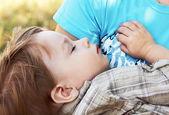 dítě spí v náručí své matky