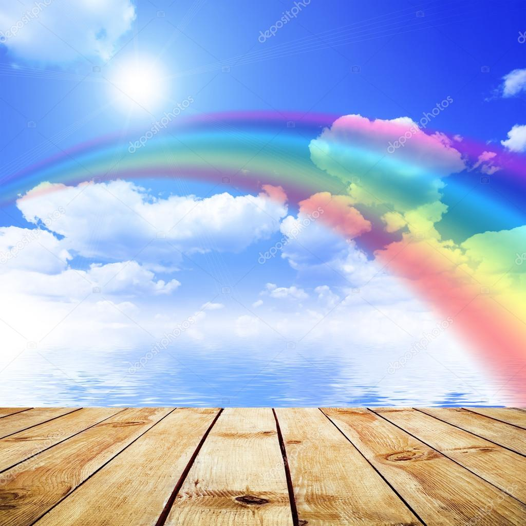 Blue sky background with rainbow and reflection in water. Wood pier