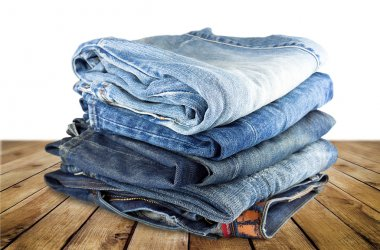Stack of various shades of blue jeans on a wood background stock vector