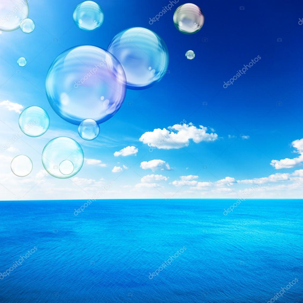 Blue sea under clouds sky with flying soap bubble