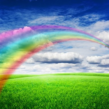 Green field under blue clouds sky with bright rainbow. Beauty nature background