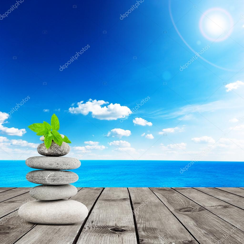 Stack of stones with mint leaf on wood planks with view on beauty sea under blue clouds sky