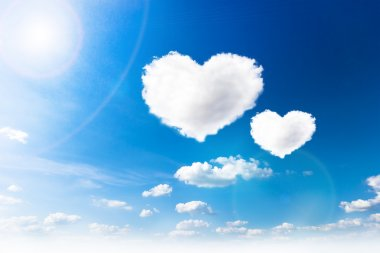 Blue sky with hearts shape clouds. Beauty natural background stock vector