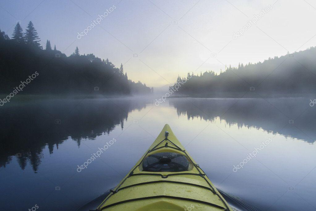 Kayak surfer on a misty lake