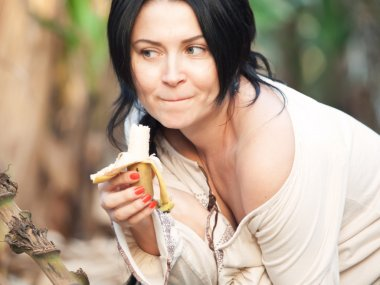 Portrait of  woman in beige blouse with banana with sense of hum