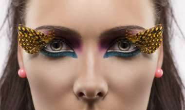 girl with feathered makeup looks in to the lens