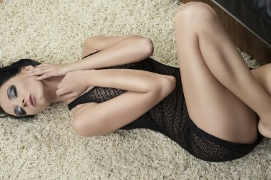 sexy brunette lying on carpet on the her back