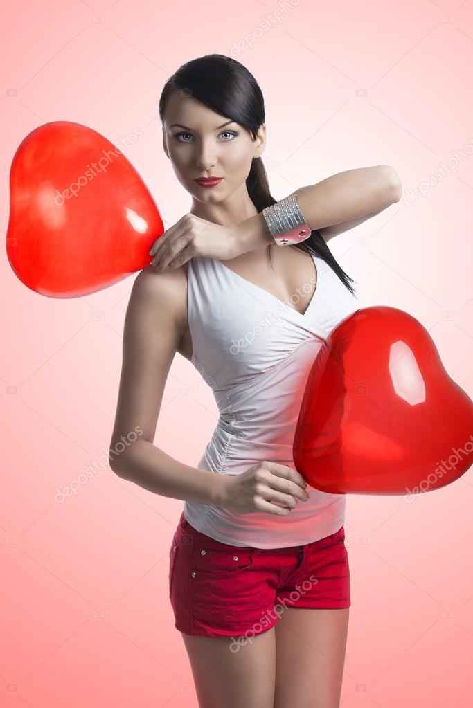 sexy brunette with heart shaped balloons on the shoulder