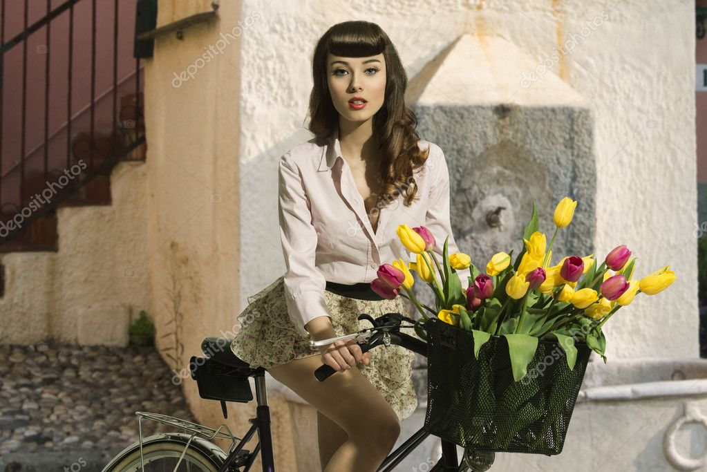 brunette pin-up on bicycle with color flowers