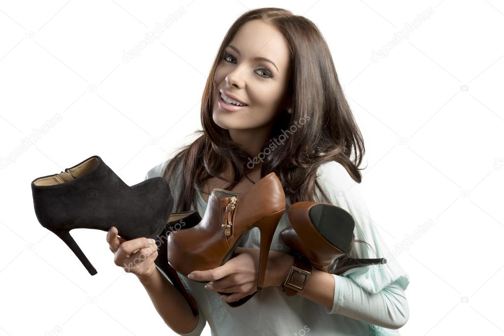 Happy brunette girl loves shopping, smiling and holding some heels shoes in her hands