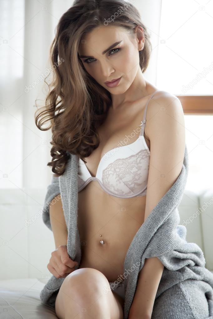 ed0206898cd2ce Beautiful and sexy young adult sensuality brunette woman in white lingerie  and grey sweater on the white sofa in window on luxury apartment — Фото від  ...