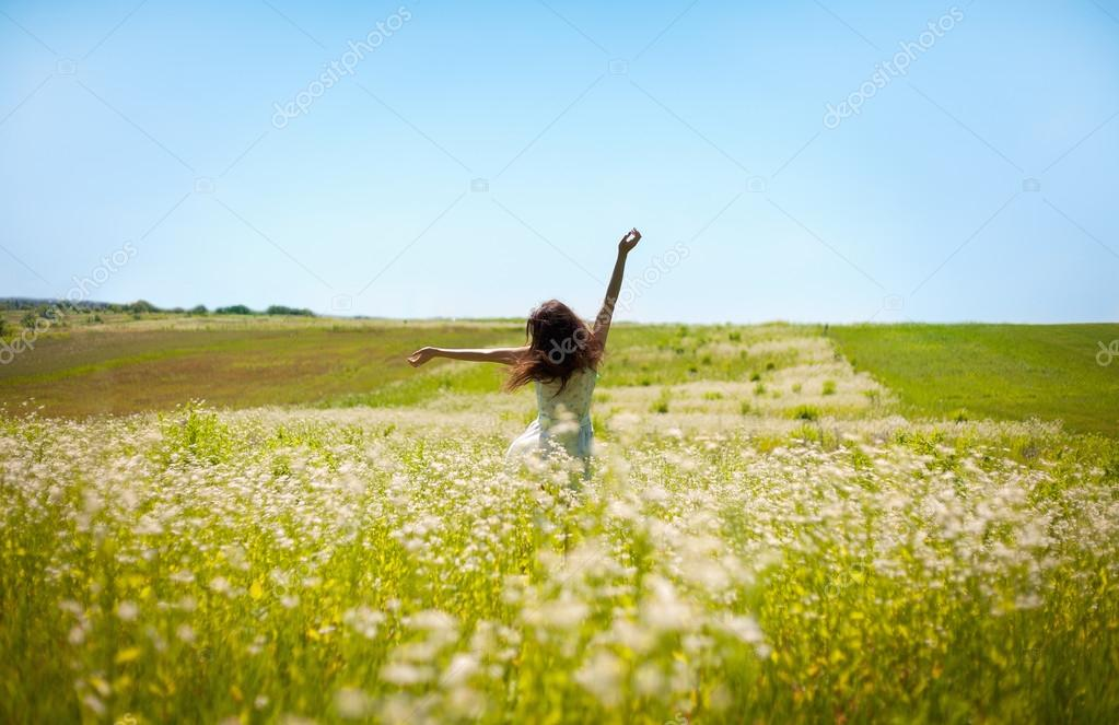 Girl lifting her hands up in the air runs across the field