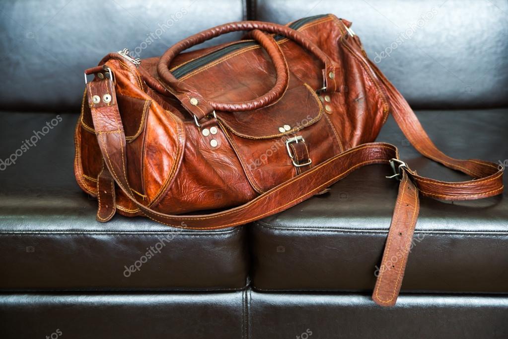 Luxusní cestovní kožená taška izolovaná na černé kožené pohovce– stock  obrázky dc77de21026