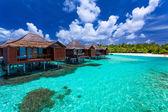 Fotografie nad vodní bungalovy s kroky do zelené korálové laguny