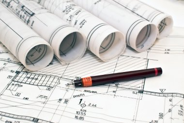 Heap of design and project drawings on table background