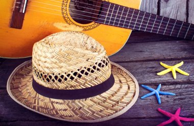 Acoustic guitar star hat and starfish on a grunge wood summer background
