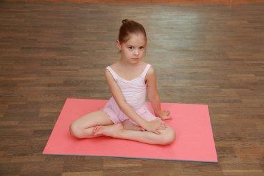 Lovely little girl doing sports exercises on the mat (stretching)