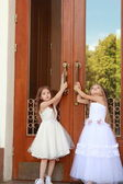 Little girls in wedding dresses and sneakers open the heavy doors outdoors