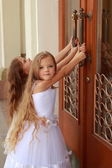 Young girl in white wedding dresses are trying to open the big doors to the building outdoors