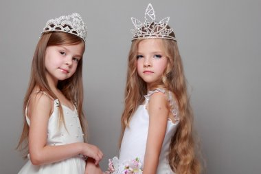 Smiling cute little girls in white dresses and a crown for the beauty contest