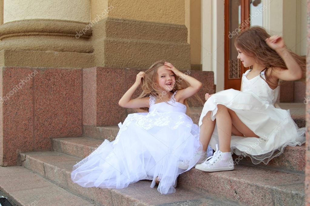 Happy Cute Little Girls With Long Hair In Long White Dresses Sitting