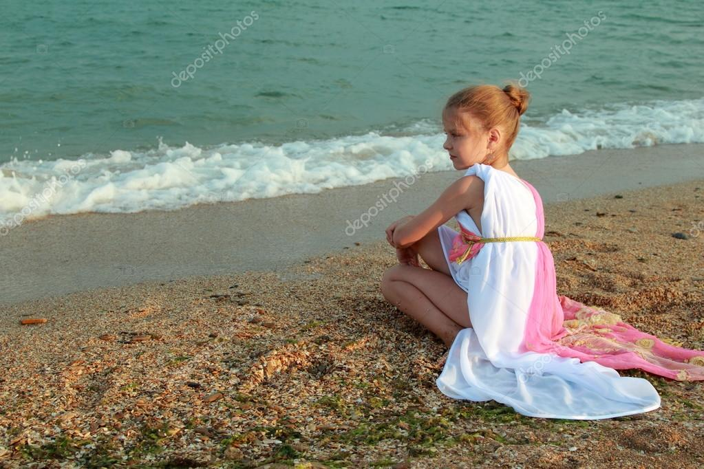 Smiling cute little girl in a beautiful dress in Greek style