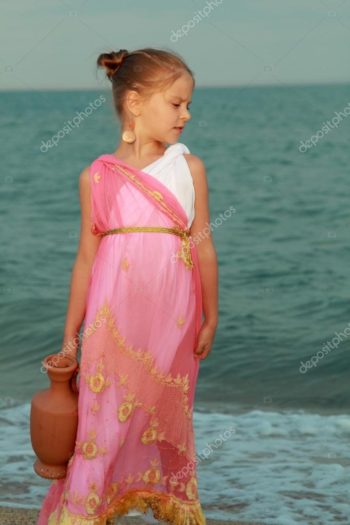 Smiling cute little girl in a beautiful dress in Greek style with an amphora