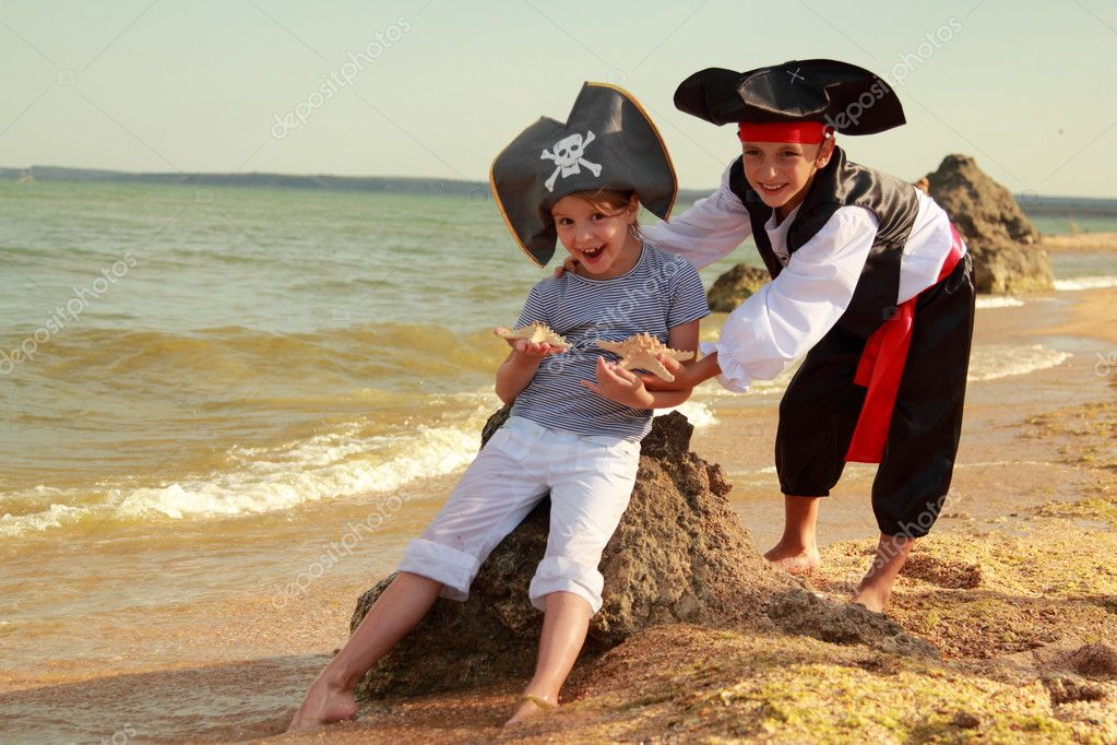 Cute little boy in a pirate costume and a little girl in a hat with a skeleton symbol of piracy