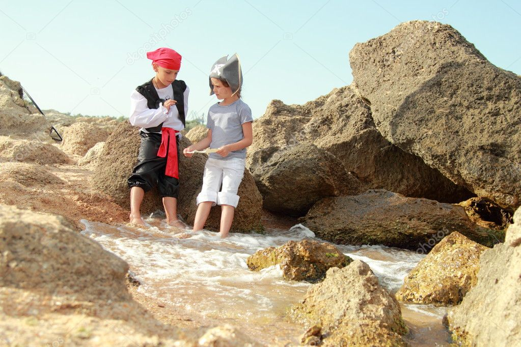 European children smiling boy and girl in fancy dress pirate looking for buried treasure