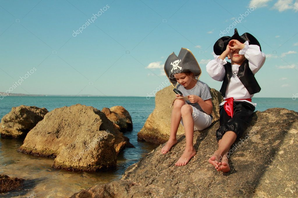 Beautiful young kids pirate boy and girl holding a pirate map