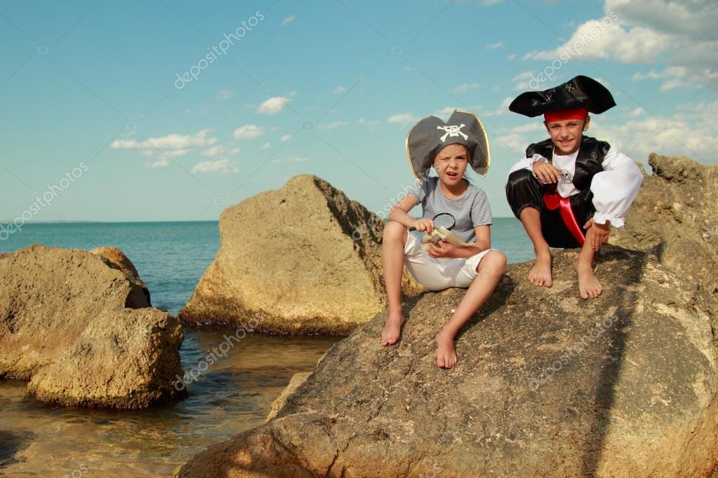 Beautiful young kids pirate boy and girl holding a pirate map and a magnifying glass