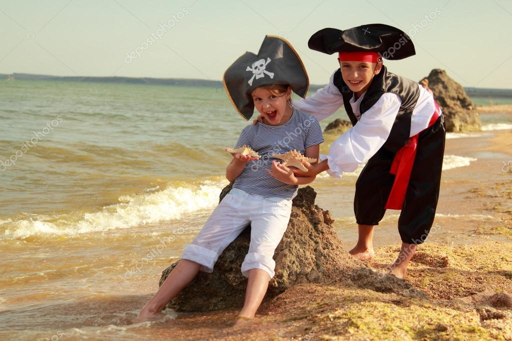 Cute little boy in a pirate costume and a little girl in a hat with a skeleton symbol