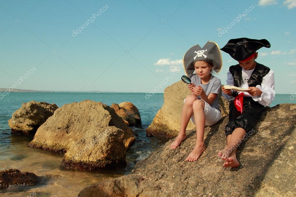 Joyful little girl and boy in fancy dress pirate