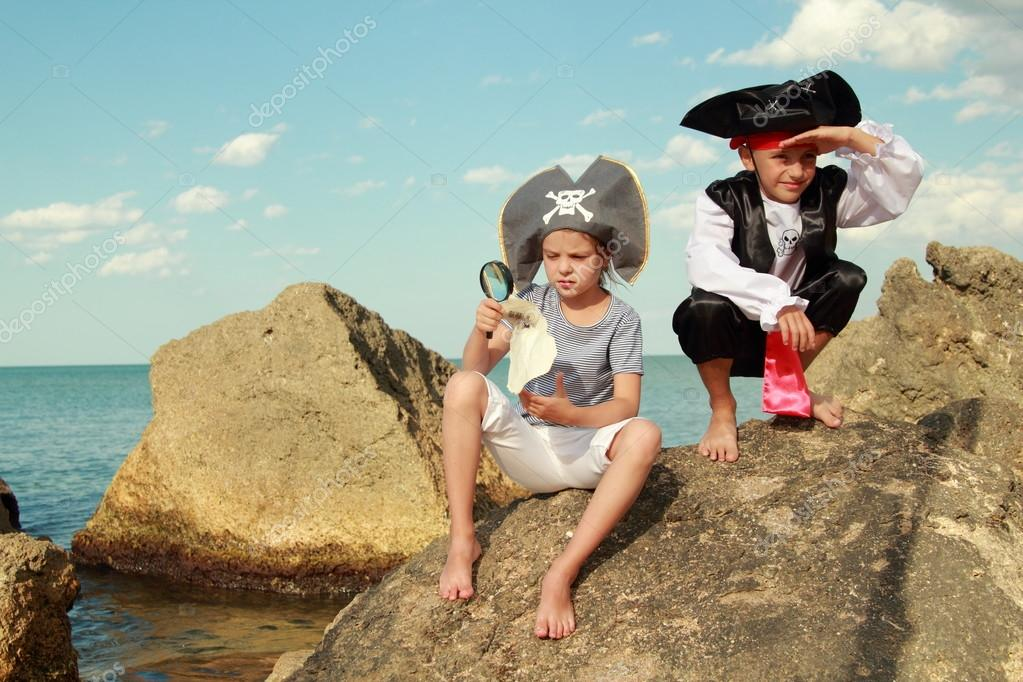 Boy and girl in a pirate costume with a map and a magnifying glass sitting on a large rock by the sea