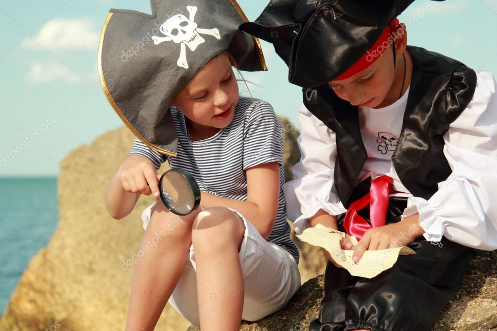 Joyful little girl and boy in fancy dress pirate sitting on the shore of the sea