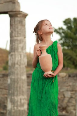 Adorable little girl in a beautiful dress with a vintage antique amphora