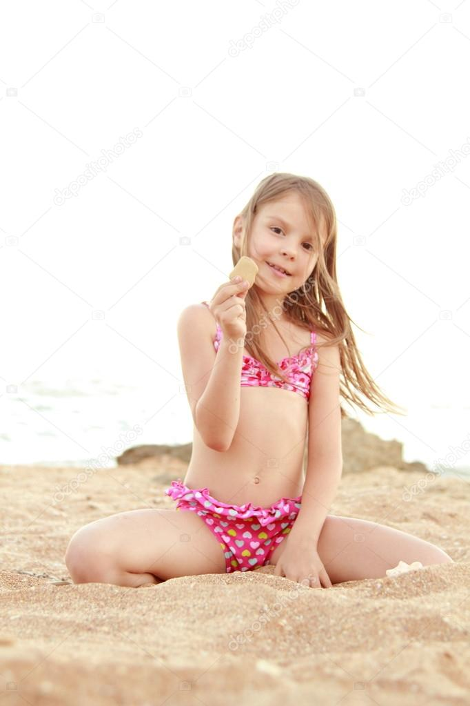 Beautiful cheerful young girl sitting on the sand and holds a large seashell.