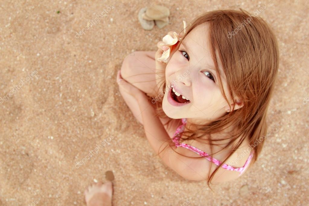 Cute smiling little girl in a bathing suit sits on a background of sea sand.