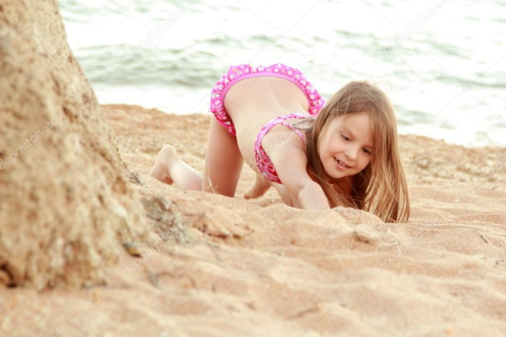 Beautiful smiling little girl in a pink swimsuit is played in the sand on the beach.