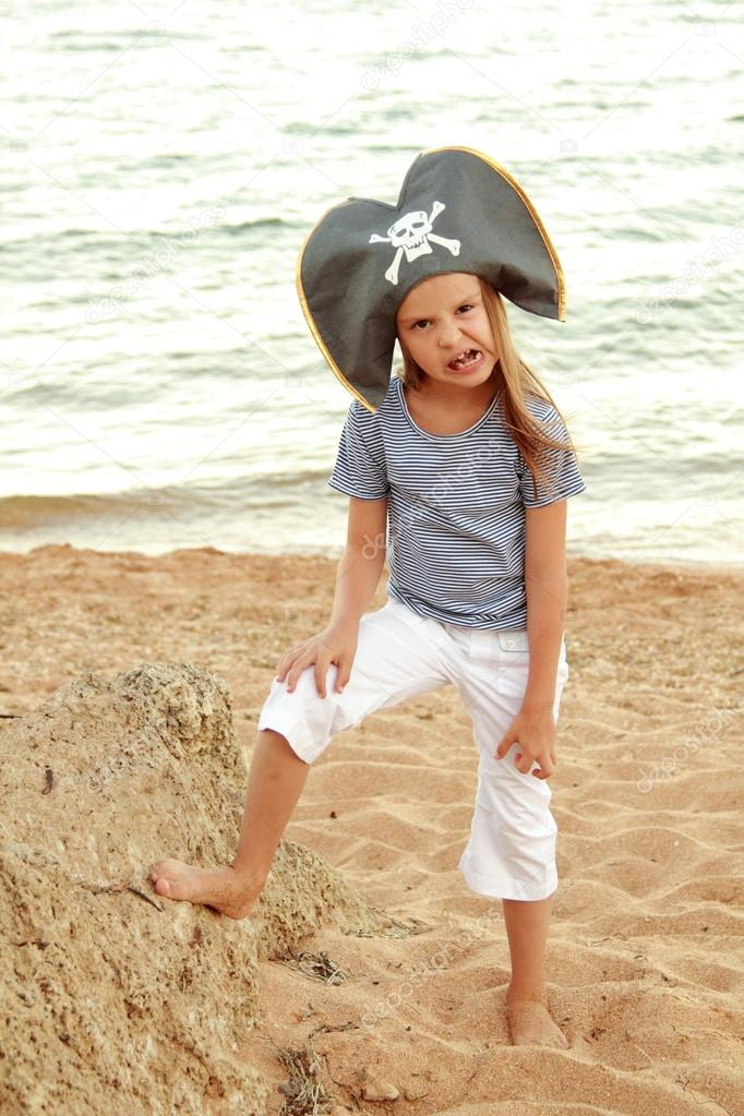 Beautiful cheerful little girl in a pirate costume is studying a treasure map.