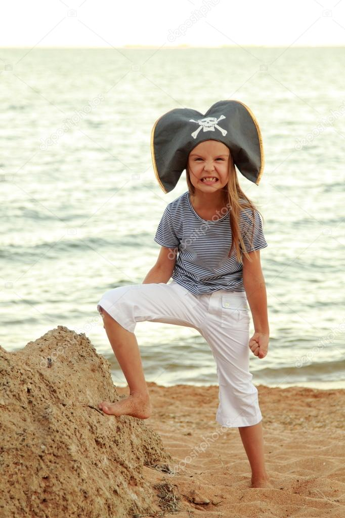 Caucasian emotional little girl in a hat with a symbol of maritime piracy.