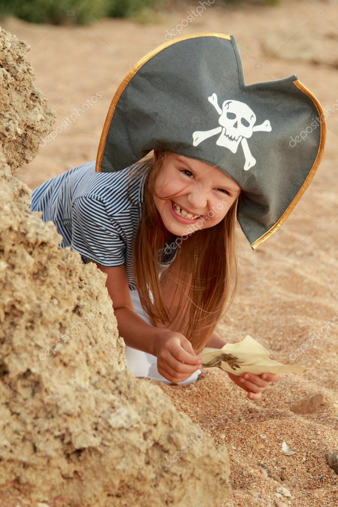 Beautiful little girl in a pirate costume with a wicked grin is holding a map.