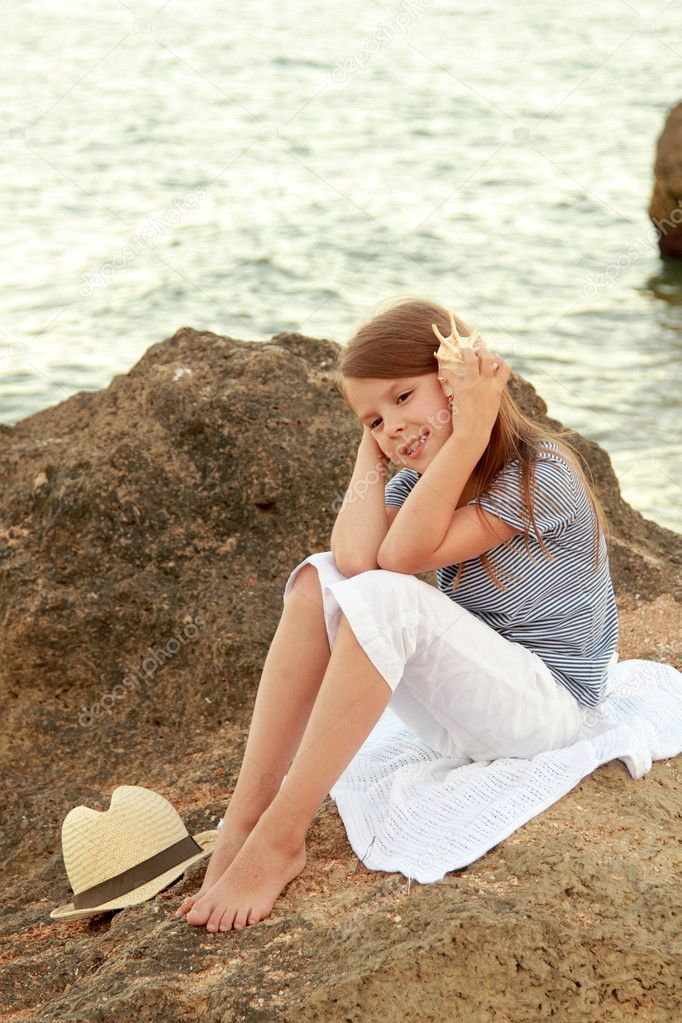 Happy cute little girl with a beautiful smile is sitting on the beach in the evening.
