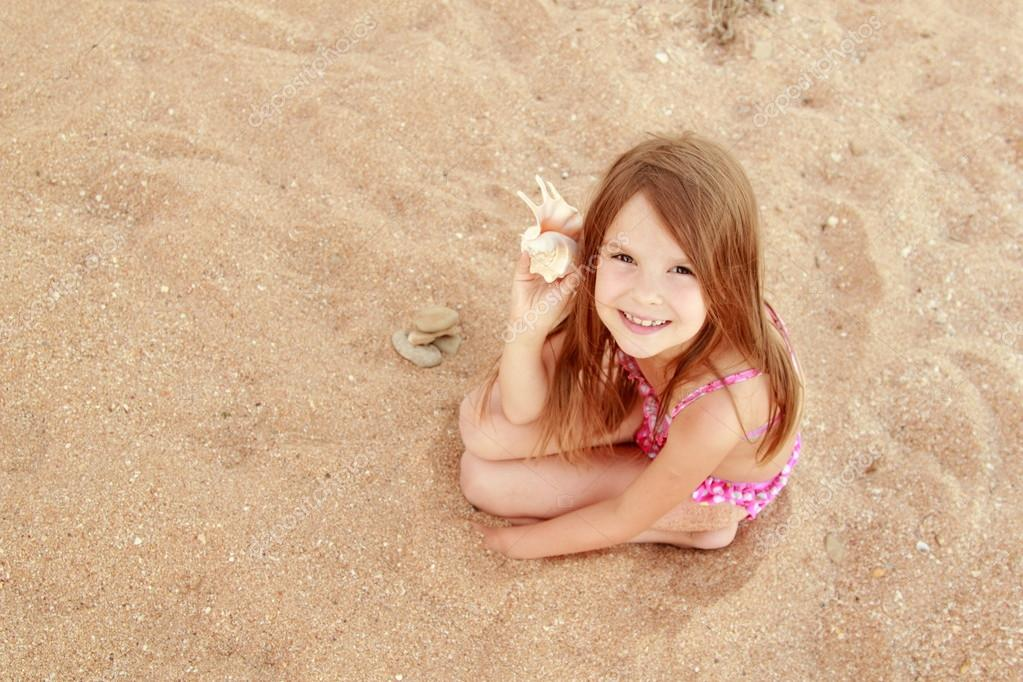 Cute smiling little girl in a bathing suit sits on a background of sea sand