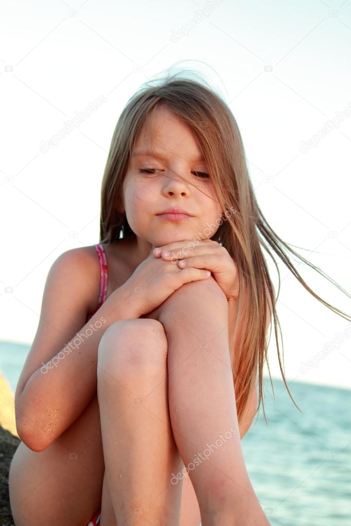 Portrait of a beautiful little girl with healthy long hair in a bathing suit on outdoors