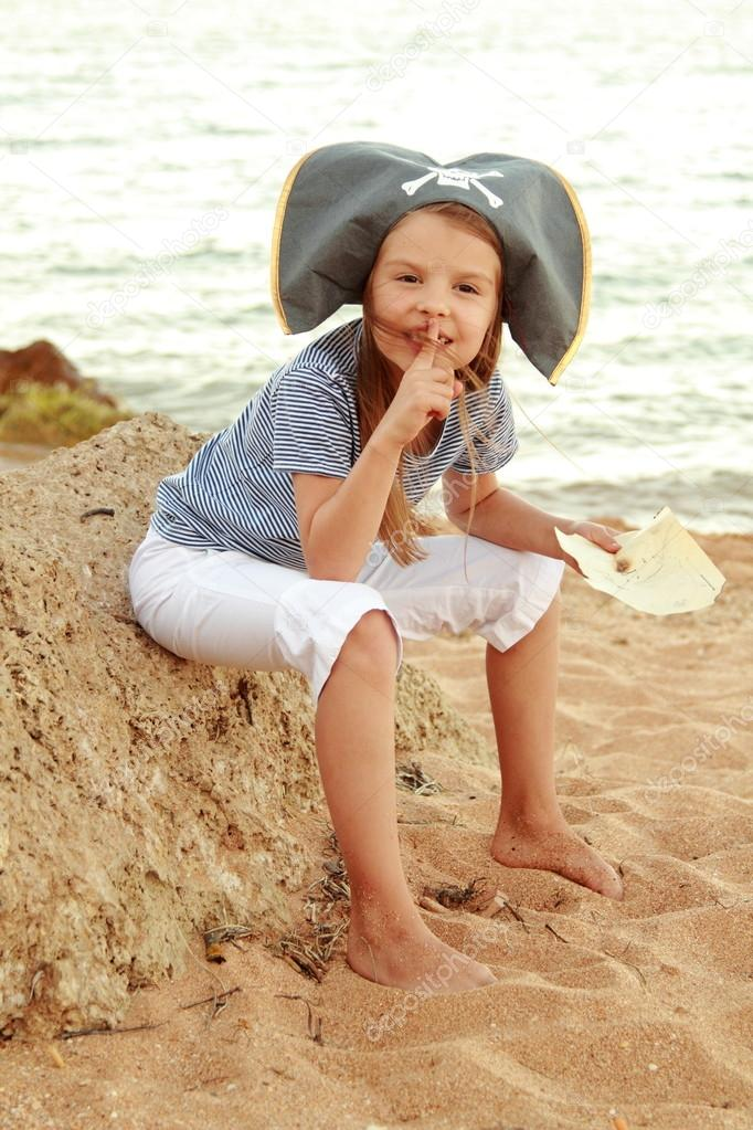 Caucasian emotional little girl in a hat with a symbol of maritime piracy