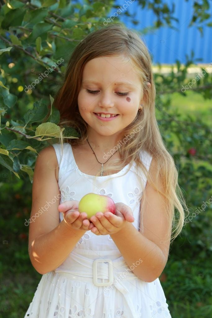 Little girl picks apples