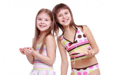 Girls holding starfish and shell