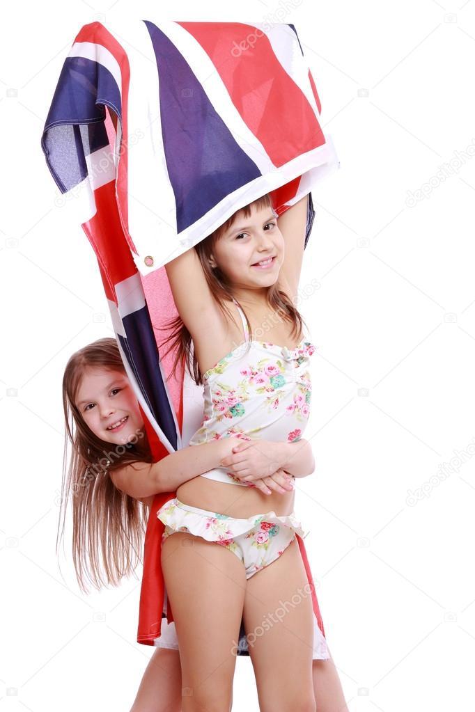 12cc4b752d8fd Эмоциональные девочки в купальниках, холдинг британский флаг на белом фоне.  Купальник с британским флагом — Фото автора Mari1Photo
